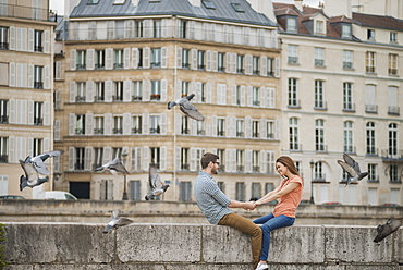 A couple, man and woman sitting on the parapet of a bridge over the River Seine, France