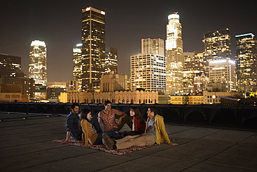 A group of friends gathered on a rooftop overlooking a city lit up at night, United States of America
