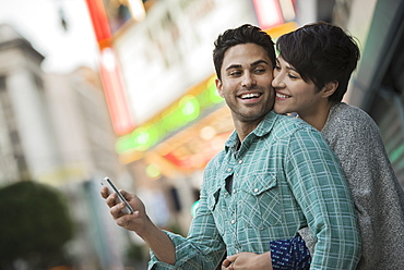 A couple, man and woman hugging on a city street. Man holding a smart phone, United States of America