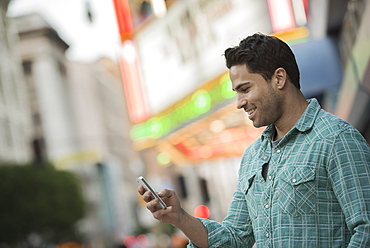 A man checking his phone on a city street, United States of America