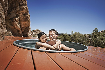 A man and woman on the terrace of an eco home, a low impact house in the desert landscape, in a sunken hot tub, United States of America