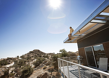 A man sitting on the roof overhang of an eco home in the desert landscape, United States of America