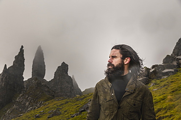 A man standing with a backdrop of rock pinnacles on the skyline, a dramatic windswept landscape and low cloud, Scotland, United Kingdom