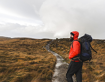 A man in winter clothing, waterproof jacket and rucksack in open countryside by a path, Scotland, United Kingdom