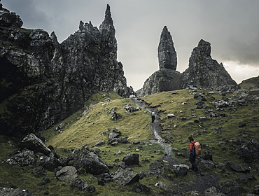 Two people with rucksacks on a narrow path rising to a dramatic landscape of rock pinnacles on the skyline towering above them, under an overcast sky with low cloud, Scotland, United Kingdom