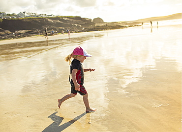 A child in a wetsuit and sunhat running on sand, England, United Kingdom