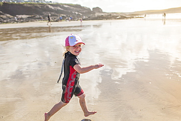 A child in a wetsuit running on sand, England, United Kingdom