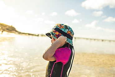 A child in a wetsuit and sunhat on a Cornish beach, England, United Kingdom