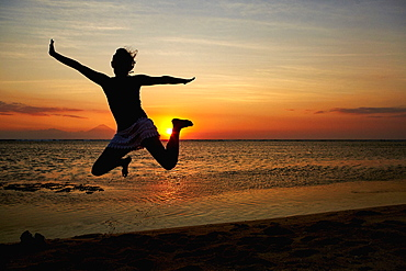 Silhouette of a woman jumping in the air, seen against a sunset sky, Bali Island, Indonesia