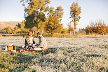 A couple, a man and woman having a winter picnic, sitting on a tartan rug.