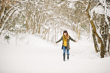 A woman walking in the snow in woodland.