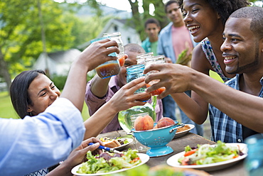 A group of adults and young people at a meal in the garden of a farmhouse. Passing plates and raising glasses, Woodstock, New York, USA