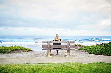Rear view of a blond woman sitting on a beach by the ocean, United States of America