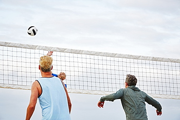 Mature men standing on a beach, playing beach volleyball, United States of America