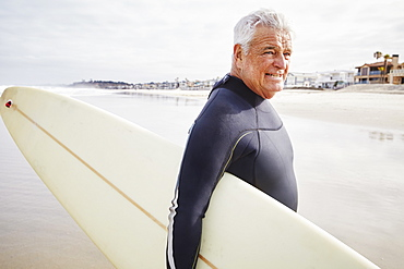 Smiling senior man standing on a beach, wearing a wetsuit and carrying a surfboard, United States of America