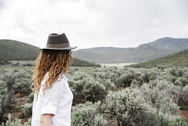 A woman in a fedora standing in an open landscape with a view of mountains woodland and scrub land, United States of America