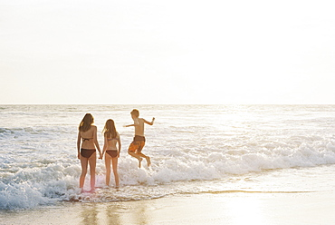 Three children playing on a sandy beach by the ocean.