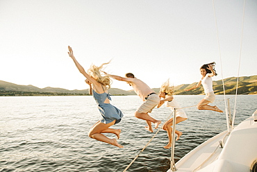 Four people jumping off the side of a sail boat into a lake.