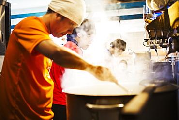 The ramen noodle shop. A chef stirring a huge pot of noodles cooking, Japan