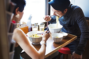 A ramen noodle cafe in a city. A man and woman seated eating noodles from large white bowls, Japan