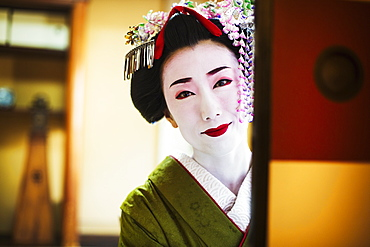 A woman dressed in the traditional geisha style, wearing a kimono and obi, with an elaborate hairstyle and floral hair clips, with white face makeup with bright red lips and dark eyes, looking in the mirror, Japan