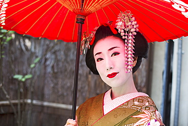 A woman dressed in the traditional geisha style, wearing a kimono with an elaborate hairstyle and floral hair clips, with white face makeup with bright red lips and dark eyes holding a red paper parasol, Japan