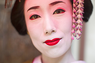 A woman made up in traditional geisha style with an elaborate hairstyle and floral hair clips, drawn eyebrows with white face makeup with bright red lips and outlined eyes, Japan