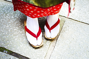 A traditional geisha woman's feet, in wooden soled sandals, with red straps and white stockings or tabi, Japan