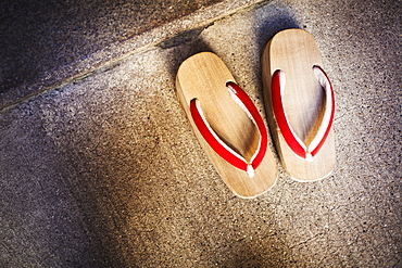 A pair of traditional wooden sandals with thick soles and red straps worn by geisha, okobo or geta, Japan