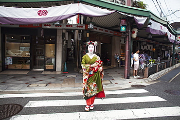 A woman dressed in the traditional geisha style, wearing a kimono and obi, with an elaborate hairstyle and floral hair clips, with white face makeup with bright red lips and dark eyes crossing a street, Japan