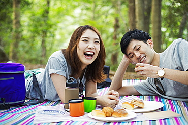 Young woman and man having a picnic in a forest, Japan
