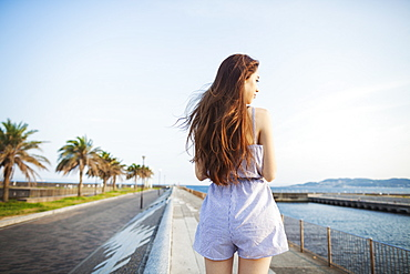 Back view of young woman with long red hair standing in open space by a road on the coast, Japan