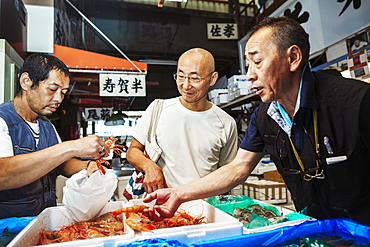 A traditional fresh fish market in Tokyo. Two people selecting shellfish for a customer to buy, filling a bag from boxes of prawns, Japan