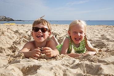 A boy and girl lying on their stomachs on the sand, laughing and looking at the camera, England