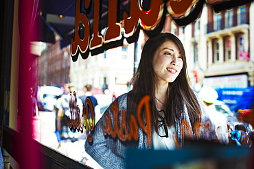 Young Japanese enjoying a day out in London, walking past a shop window, United Kingdom