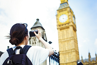 Young Japanese woman enjoying a day out in London, taking a picture of Big Ben, United Kingdom