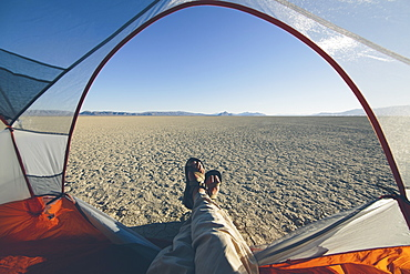 Man reclining in camping tent, expansive desert and playa in distance, Black Rock Desert, Nevada, United States of America