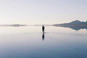 Man walking on vast and flooded Bonneville Salt Flats, Utah, United States of America