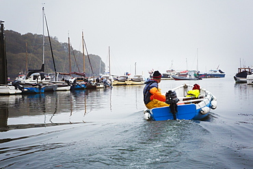 Sailing boats and motorboats moored in the Fal estuary, A fisherman in a small boat, Fal Estuary, Cornwall, England