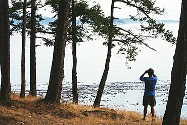 Man standing on a beach, looking through binoculars, San Juan Islands in the distance, Washington, USA.