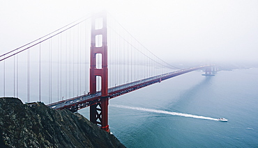 The Golden Gate bridge in the mist, with a boat sailing underneath.