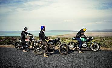 Three men wearing open face crash helmets sitting on cafe racer motorcycles on a rural road, United States of America
