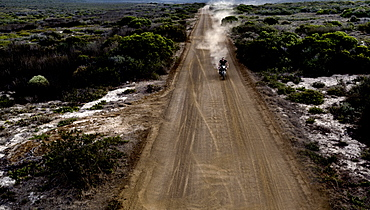 Landscape with man riding cafe racer motorcycle along dusty dirt road, United States of America