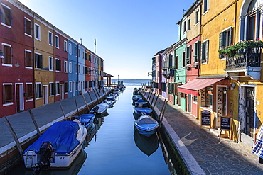 Small motorboats moored in narrow canal lines with colourful houses, Venice, Italy, Venice, Italy
