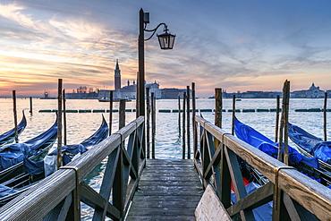 Gondolas moored on a canal in Venice, Italy, at sunrise, Venice, Italy