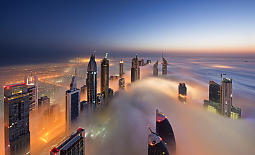 View of illuminated skyscrapers above the clouds in Dubai, United Arab Emirates at dusk, Dubai, United Arab Emirates