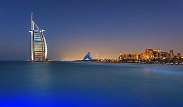Cityscape of Dubai, United Arab Emirates at dusk, coastline of Persian Gulf with illuminated Burj Al Arab skyscraper in the distance, Dubai, United Arab Emirates