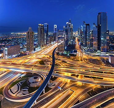 Cityscape of Dubai, United Arab Emirates at dusk, with skyscrapers and illuminated highways in the foreground, Dubai, United Arab Emirates
