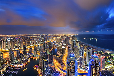 Cityscape of the Dubai, United Arab Emirates at dusk, with illuminated skyscrapers and coastline of the Persian Gulf, Dubai, United Arab Emirates