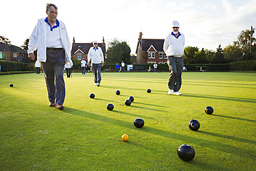 Three lawn bowls players, men walking across the green, the playing surface, at an end with bowls clustered around the yellow jack ball, England, United Kingdom